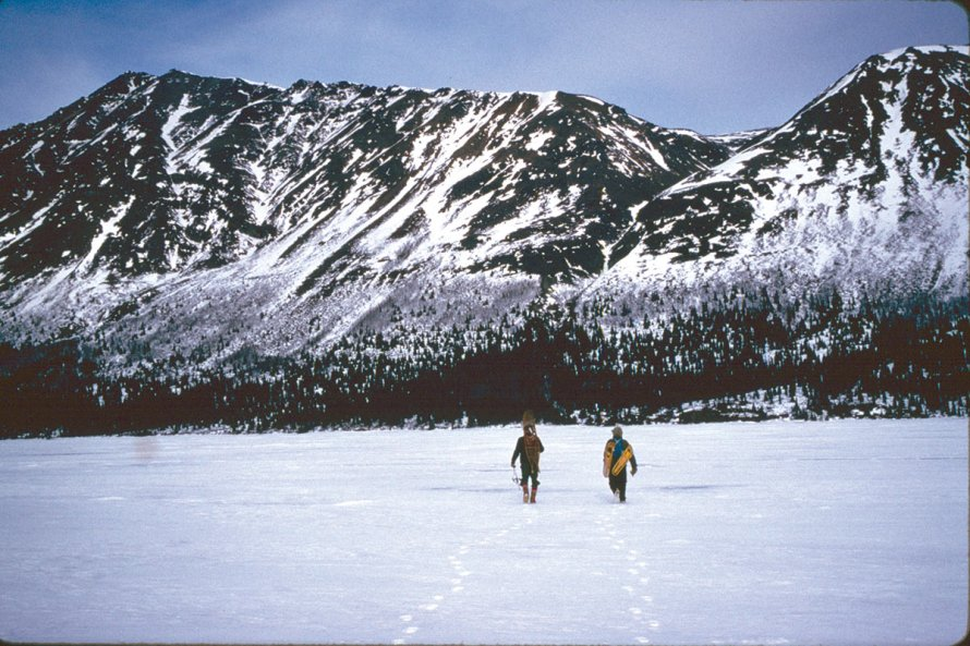 Snowshoes across their backs, Dick Proenneke and Leon Alsworth III cross Upper Twin Lake for a late winter hike to the top of Falls Mountain.
