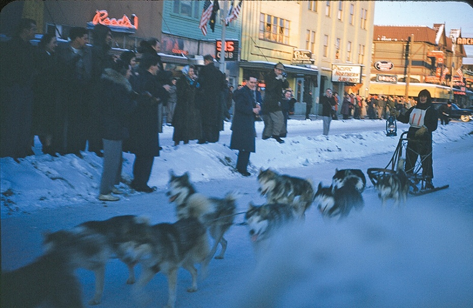 "A color photograph the sprint race at Fur Rondy. The exact date is not known. Late 1940's - early 1950's.   The Fur Rendezvous  ""Fur Rondy"" winter festival began in 1935 in Anchorage. Rendezvous is a French word meaning ""a meeting at an agreed time and place, typically between two people."""