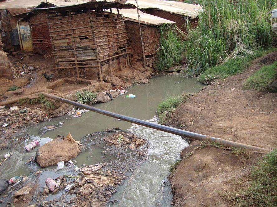 Ivory Coast, Africa. A common pit latrine emptying into a waterway. The toilet is located in the nearest hut, and empties directly into the stream.