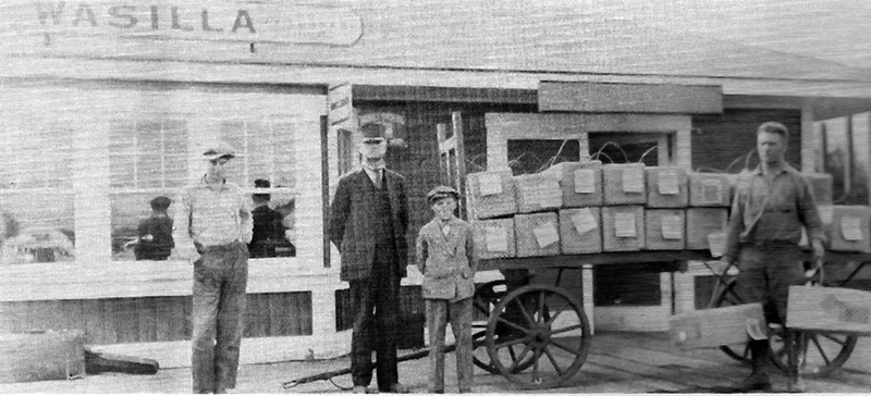 A $7,000 shipment of mink at the Wasilla train station. Heinie holding two crates at far right.
