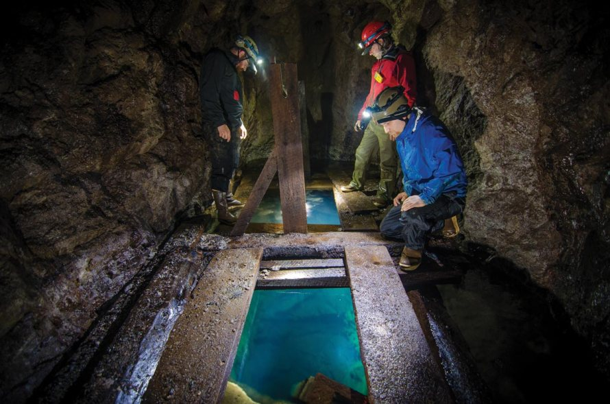 Members of the Juneau's Hidden History Hardcore team examine a water filled winze in a mine adit. We built an underwater camera boom to lower down the winze and to take underwater pictures and video. While diving is always an option, it is very dangerous in flooded mine areas.    –The Douglas Island Prospect, Juneau